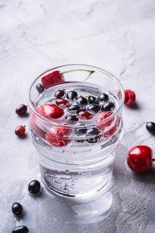 Bevanda fresca e fredda di acqua frizzante con ciliegia, lampone e ribes bacche in vetro trasparente sulla pietra tavolo in cemento, bevanda dietetica estiva, macro vista angolare