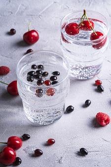 Bevanda fresca e fredda di acqua frizzante con ciliegia, lampone e ribes in due vetri trasparenti su pietra superficie in calcestruzzo, bevanda dietetica estiva, macro vista