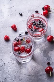 Acqua frizzante fresca e fredda bevanda con ciliegia, lampone e bacche di ribes in due vetri trasparenti sul tavolo in cemento di pietra, bevanda dietetica estiva, vista angolare