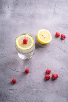 Bere acqua frizzante fredda fresca con limone, frutti di lampone in vetro