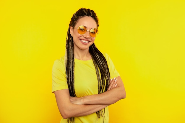 Colore fresco. donna felice con lunghi dreadlocks in posa su sfondo giallo.