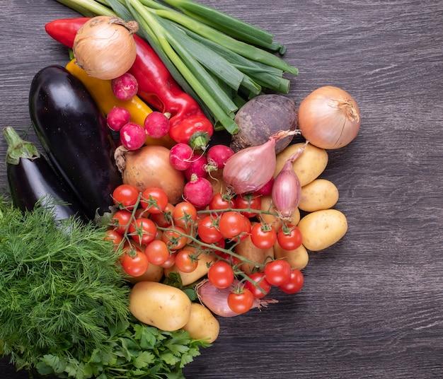Verdure biologiche colorate fresche su uno sfondo di tavolo in legno rustico, agricoltura e concetto di cibo sano.