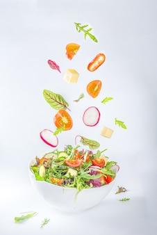 Insalata di primavera colorata fresca - avocado, pomodoro, lattuga, cipolla, ravanello, cetriolo, formaggio. in una ciotola bianca su sfondo bianco copia spazio, con ingredienti di levitazione