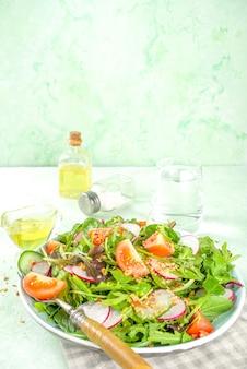 Insalata di primavera colorata fresca con pomodori, avocado, noci, cetrioli, ravanelli primaverili, su sfondo verde chiaro spazio copia. concetto di cibo sano di dieta di primavera
