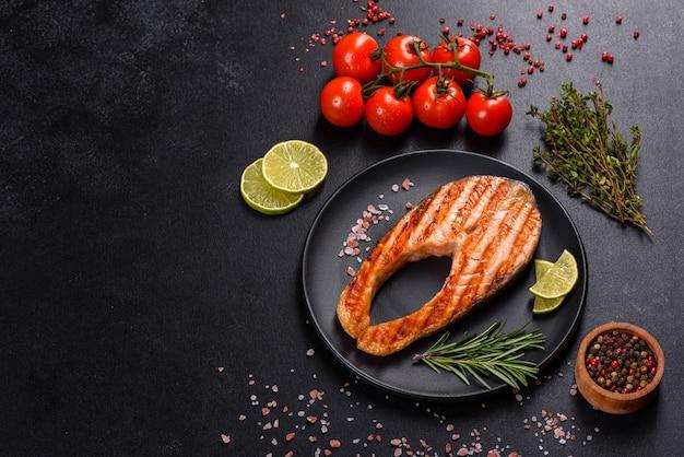 Bistecca di color salmone deliziosa cotta fresca con spezie ed erbe aromatiche cotte su una griglia