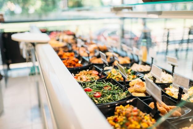 Cibo cucinato fresco in negozio, nessuno. vetrina con insalate preparate e prodotti a base di carne nel mercato