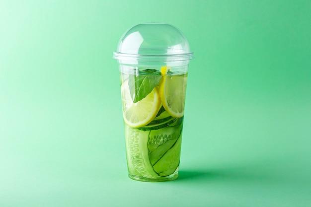 Bevanda disintossicante fresca e fresca con cetriolo, limone e basilico in tazza di plastica su verde
