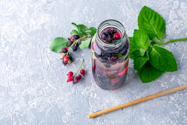 Bevanda detox fresca e fresca con vari frutti di bosco in bottiglia di vetro e paglia di carta. gustosa acqua infusa o limonata. una corretta alimentazione e una sana alimentazione. zero sprechi, concetto ecologico.