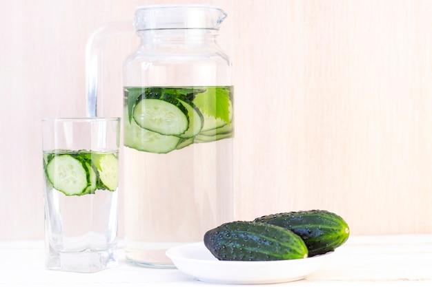 Bevanda fresca e fresca al cetriolo al limone con acqua, cocktail, bevanda disintossicante, limonata in una brocca di vetro e un bicchiere
