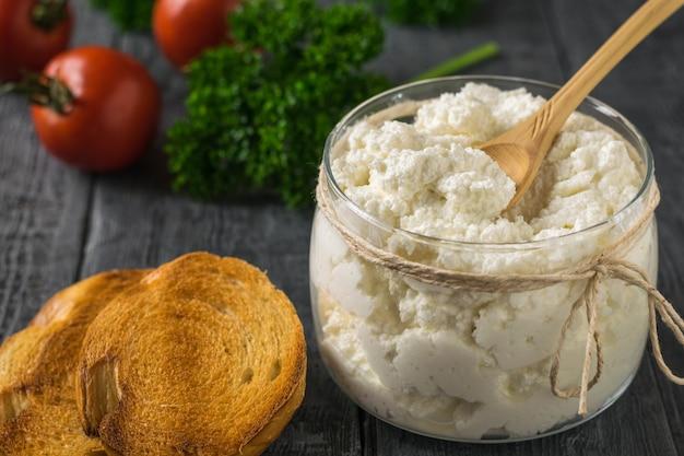 Ricotta fresca, pane tostato e verdure su un tavolo di legno.