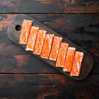 Surimi di carne di granchio fresca con set di granchio blu nuoto, sul tagliere di legno, sul tavolo di legno scuro, vista dall'alto laici piatta Foto Premium
