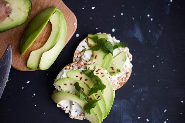 Pane croccante fresco con crema di formaggio, avocado e semi su una superficie nera