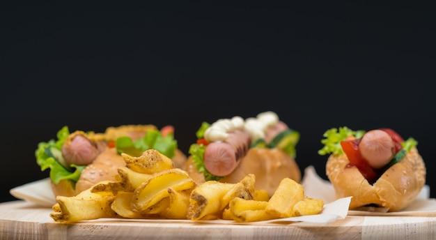Fresco e croccante patatine fritte infornate su una tavola di legno con hot dog assortiti con diverse guarnizioni in una vista ad angolo basso