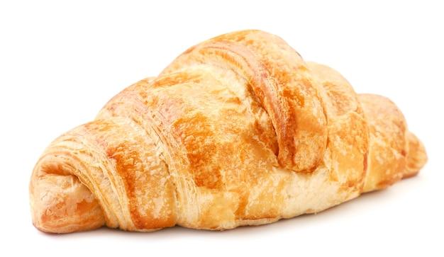 Primo piano fresco del croissant su un piatto bianco. isolato