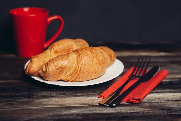 Croissant fresco su una colazione della tazza di caffè degli utensili della cucina del piatto. foto di alta qualità