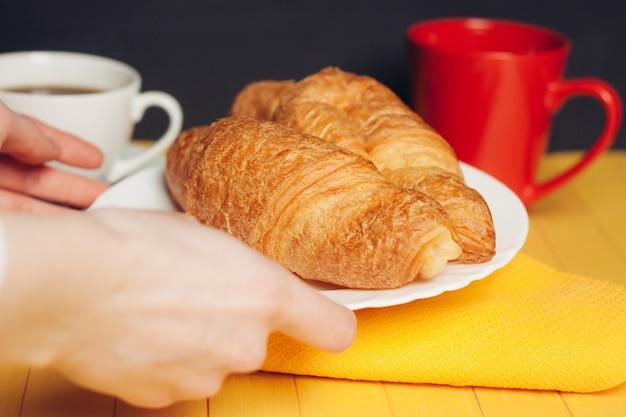 Croissant fresco su una tazza di caffè degli utensili della cucina del piatto