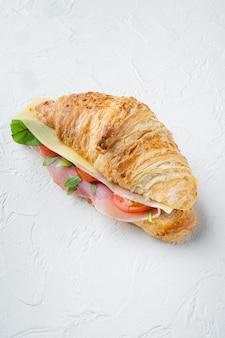 Panino di croissant fresco con prosciutto, formaggio e set di foglie di insalata, su priorità bassa di pietra bianca, con lo spazio della copia per testo
