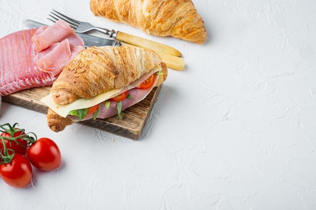 Croissant freschi sandwich con prosciutto, formaggio e foglia di insalata insieme, con erbe e ingredienti, su pietra bianca sullo sfondo, con copia spazio per il testo