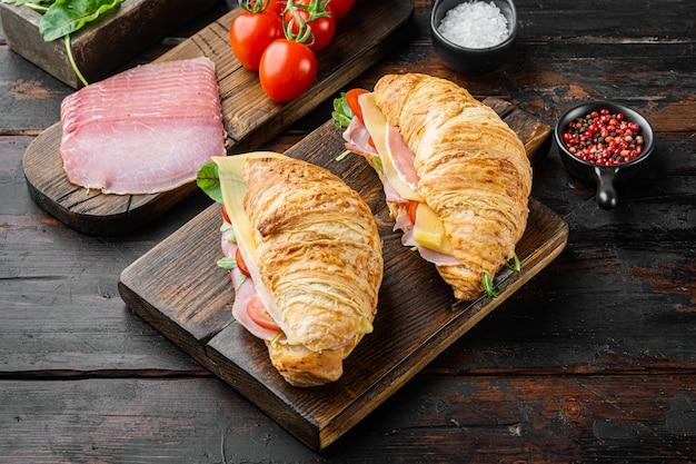 Croissant o panino fresco con insalata, prosciutto, jamon, set di prosciutto, con erbe e ingredienti, su un vecchio tavolo di legno scuro