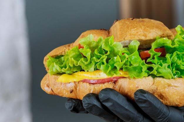 Croissant fresco con prosciutto e insalata nella mano di un cameriere in un guanto nero