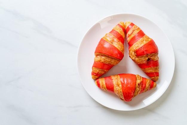Croissant fresco con salsa di marmellata di fragole sul piatto