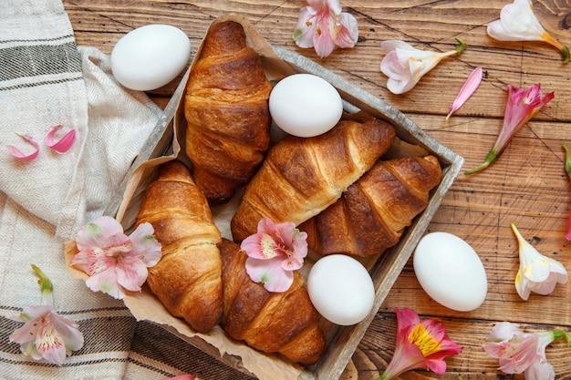Croissant freschi, uova e fiori in un vassoio su un tavolo in legno vista dall'alto