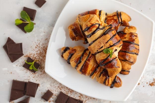 Croissant freschi con sciroppo di cioccolato su uno sfondo luminoso, copia spazio, vista dall'alto. concetto di dessert di cucina francese.