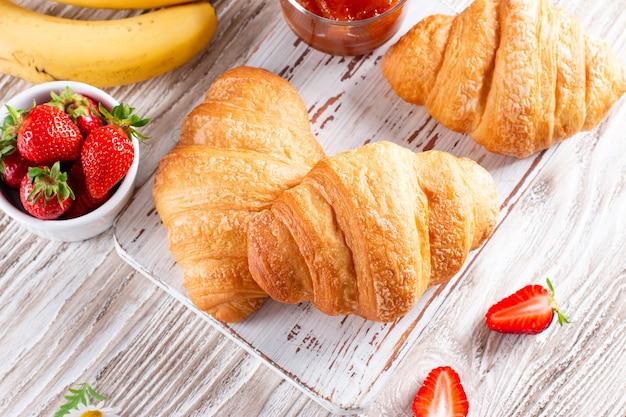 Croissant freschi con marmellata per colazione su tavola di legno