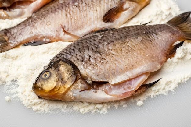 Carassio fresco con sale grosso nella farina su un tagliere bianco. cucinando, da vicino. copia spazio