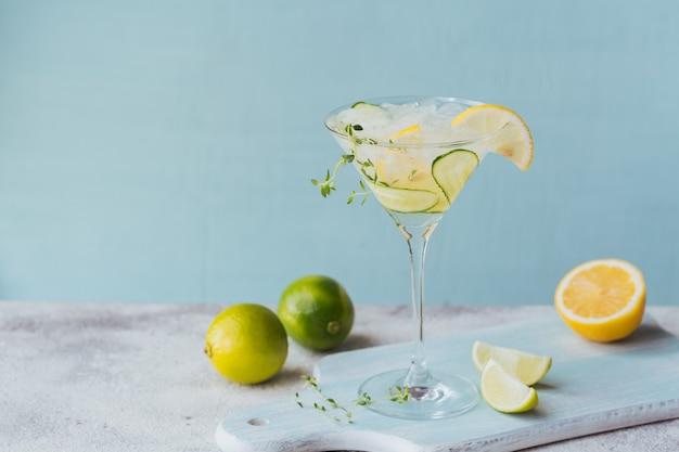 Cocktail di cetriolo fresco in un bicchiere, cocktail estivo con cubetti di cetriolo, lime, timo e ghiaccio