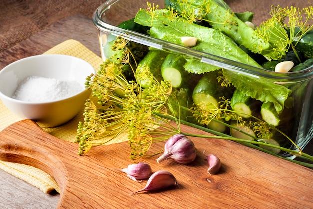 Cetrioli freschi con erbe e spezie preparati per il decapaggio in contenitore di vetro quadrato