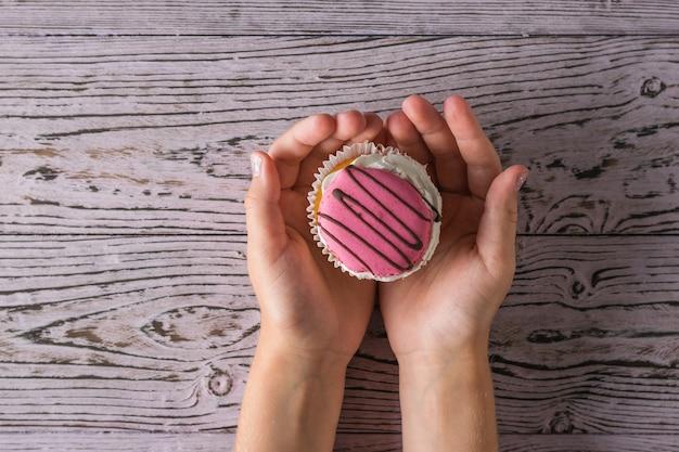 Cupcake fresco nelle mani di un bambino su un tavolo di legno