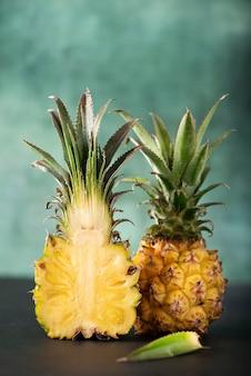Mini ananas fresco tagliato su sfondo verde, close-up