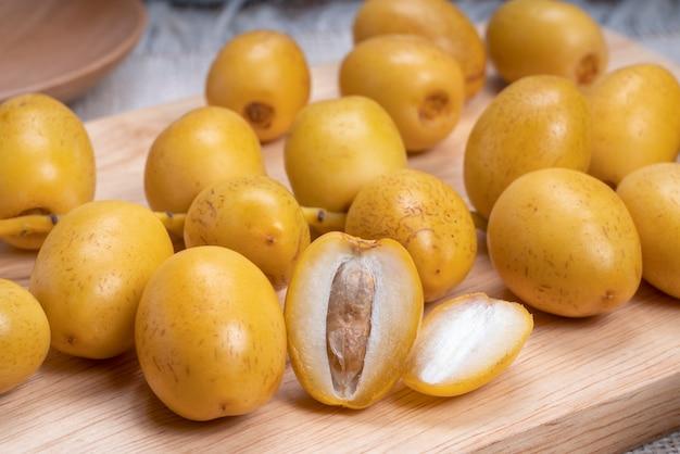 Frutta fresca della palma da datteri su un piatto di legno, frutta gialla dolce della palma da datteri.