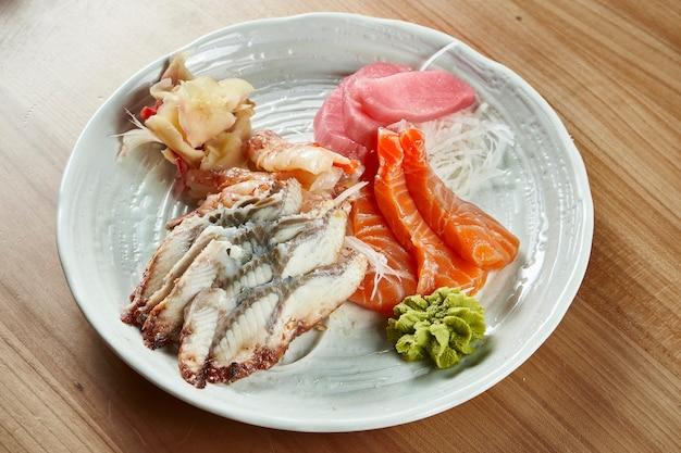 Gamberi, tonno, salmone e anguilla assortiti freschi e deliziosi di sashimi con ravanello daikon e wasabi in una ciotola bianca su una superficie di legno