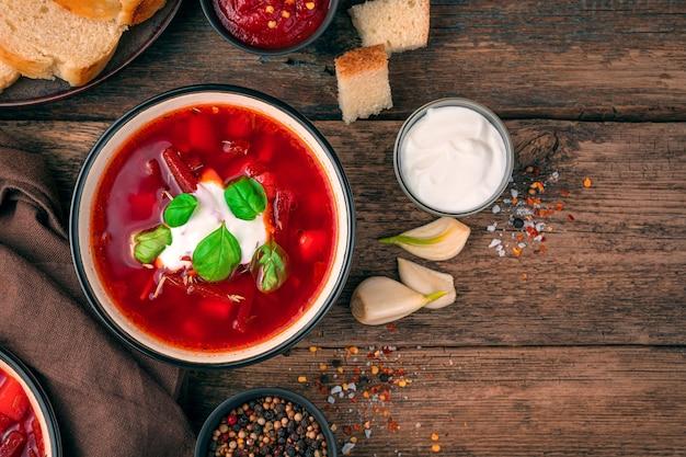 Zuppa di barbabietole fresca e deliziosa con panna e basilico su un fondo di legno marrone. concetto di cucina.