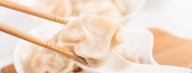 Maiale bollito fresco e delizioso, gnocchi di gyoza di gamberi su sfondo bianco con salsa di soia e bacchette, primo piano, stile di vita. concetto di design fatto in casa.