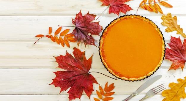 Torta di zucca fatta in casa deliziosa fresca su fondo di legno bianco con fogliame di autunno