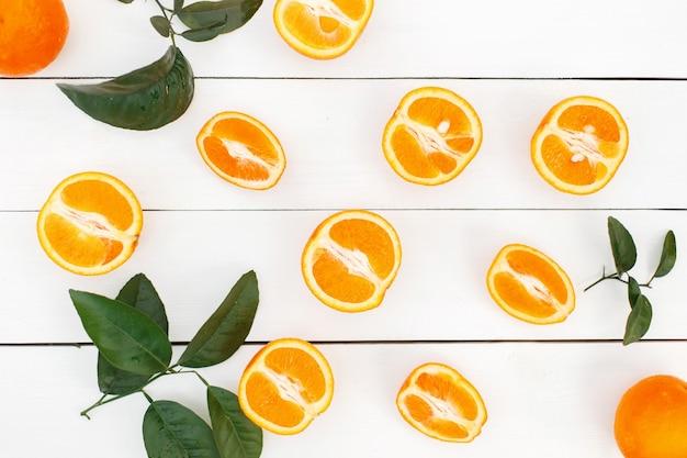 Arancia fresca deliziosa con foglie su un tavolo di legno bianco