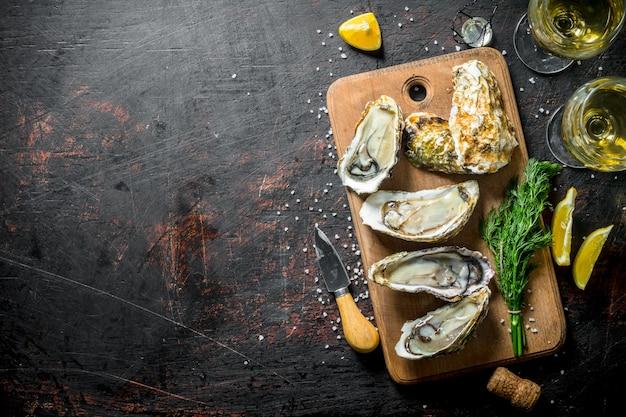 Ostriche fresche deliziose con vino bianco, limone e aneto sulla tavola rustica nera
