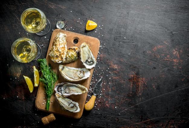 Deliziose ostriche fresche con vino bianco, limone e aneto. sul tavolo rustico scuro