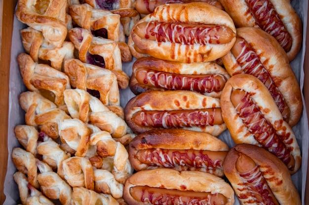 Deliziosi pasticcini freschi e hot dog su carta da forno vista dall'alto. gustoso cibo di strada