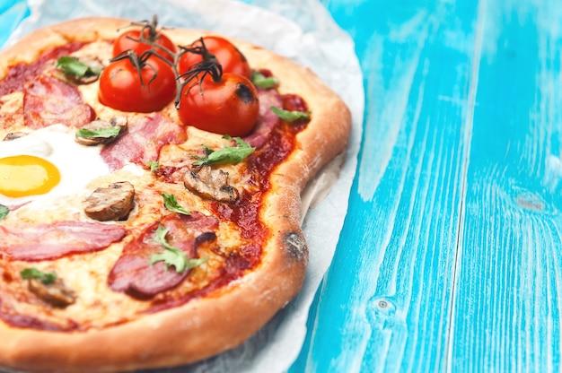Deliziosa pizza fresca dal forno con uova, prosciutto e pomodoro