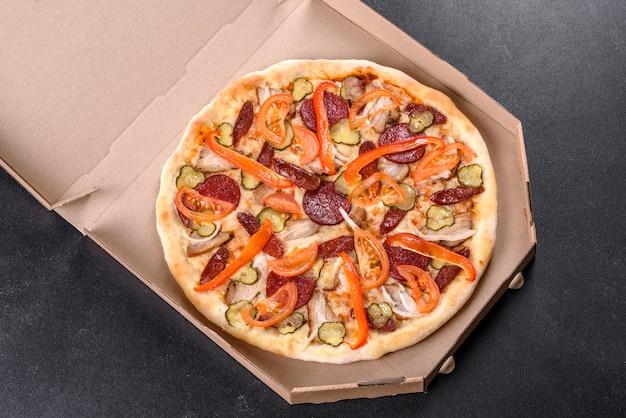 Deliziosa pizza fresca fatta in un forno con focolare con salsiccia, pepe e pomodori. cucina mediterranea