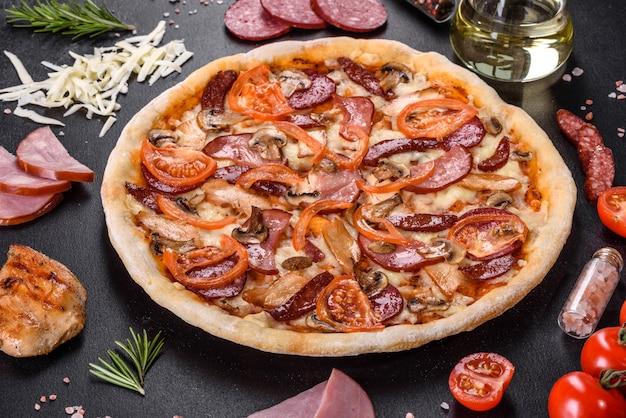 Pizza deliziosa fresca fatta in un forno con focolare con salsiccia, pepe e pomodori. cucina mediterranea