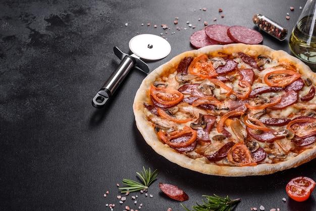 Deliziosa pizza fresca fatta in un forno con focolare con salsiccia, pepe e pomodori