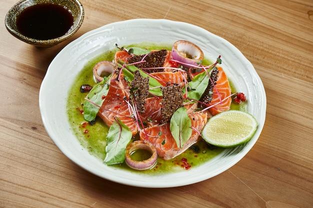 Sashimi fresco e delizioso di salmone e con salsa verde e wasabi in una ciotola bianca su una superficie di legno