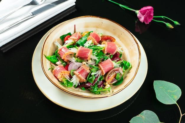 Insalata tataki fresca e deliziosa con tonno, lattuga, cipolla rossa, pomodorini e ravanello daikon. insalata saporita dei frutti di mare di cucina giapponese in ciotola gialla su fondo scuro.