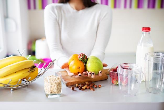 Una giovane donna vicino a un bancone della cucina tiene in mano frutta fresca e diversificata che ha tutti gli ingredienti che un frullato dovrebbe avere.