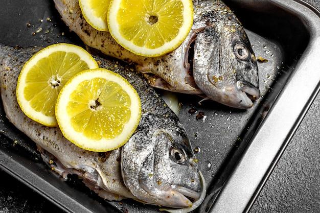 Pesce dorado fresco con limone su una teglia